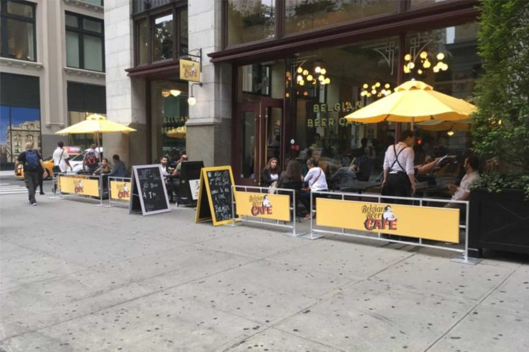 Belgian Beer Cafe outdoor seating area with sidewalk barriers and cafe partitions and umbrellas by NYC Signs & Awnings